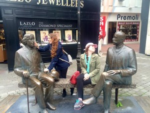Kayla and a friend with bronze statues of two gentlemen.