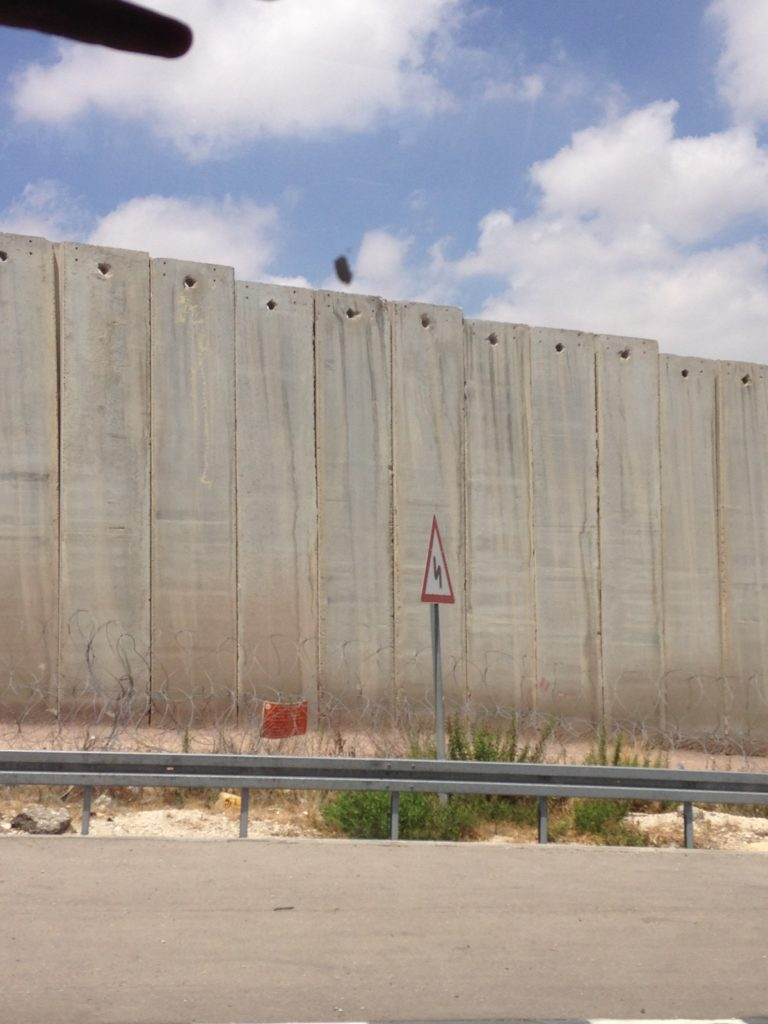Driving past a section of wall separating the West Bank from Israel.