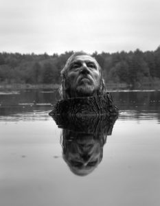 Arno Minkkinen's head emerging from a stump in the water.