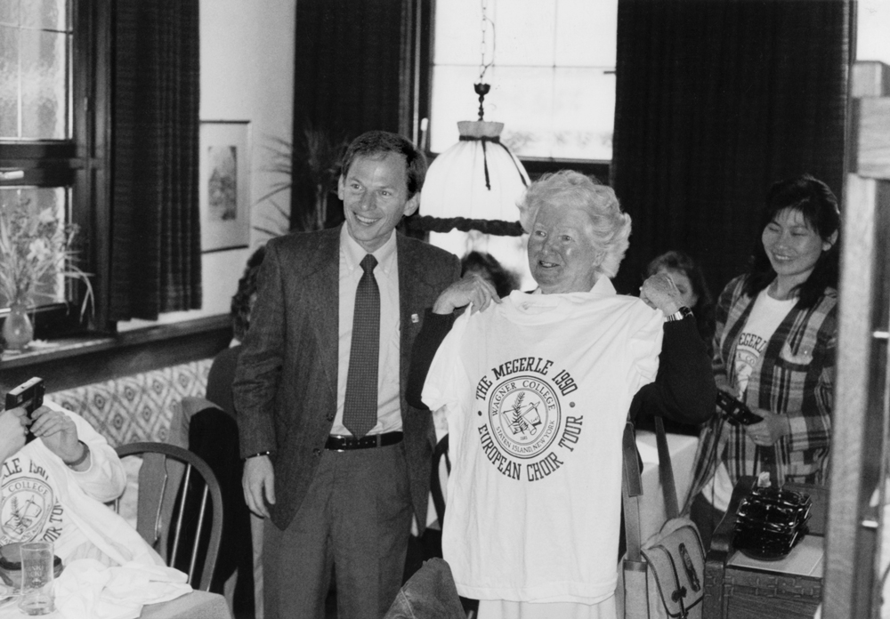 David Castleberry stands with Martha Megerle, holding a commemorative t-shirt.