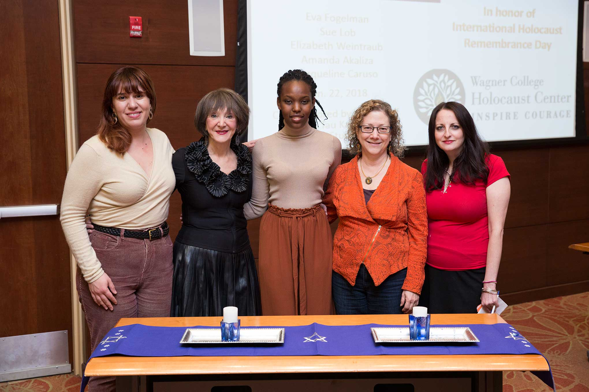 The five women stand together behind a table with a blue runner and candles.