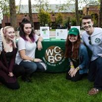 Students at table with WCBG logo