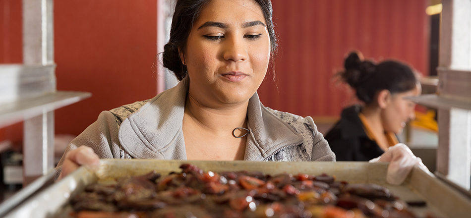 A student looks at a tray of vegetables.