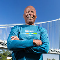 Arnold Obey '68 smiles at the camera in front of the Verrazano bridge on a sunny day.