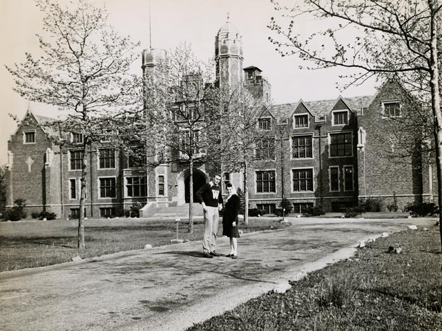 A black-and-white photo of two people standing on a path in front of Main Hall, with grass and bare trees on either side.