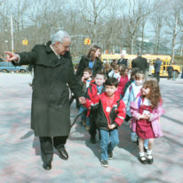 Molinari leads children by the hand onto campus.